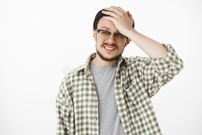 Cintura-acima disparada do indivíduo virado cocnerned e incomodado com barba e do bigode em guardar preto do beanie e dos vidros  imagens de stock