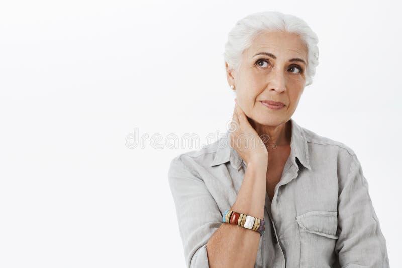 Cintura-acima disparada do nostálgico e da mulher superior bonito sábia pensativa com o cabelo branco que toca no pescoço que olh fotografia de stock royalty free