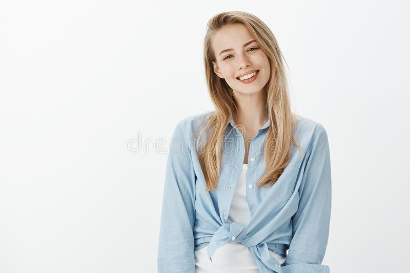 A cintura-acima disparou da amiga bonita bonito com cabelo louro, inclinando a cabeça e sorrindo alegremente ao estar ocasionalme foto de stock