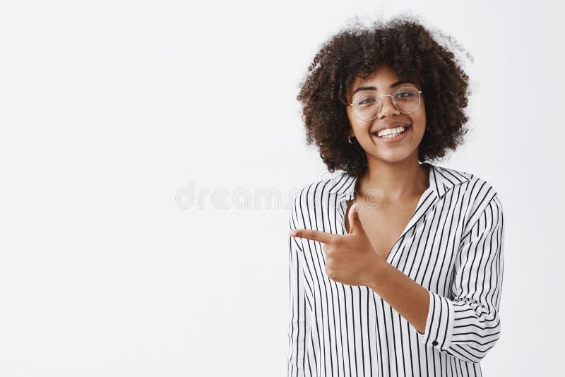 A cintura-acima disparou da menina afro-americano bonita amigável e polida nos vidros com cabelo encaracolado em escritório listr imagens de stock royalty free