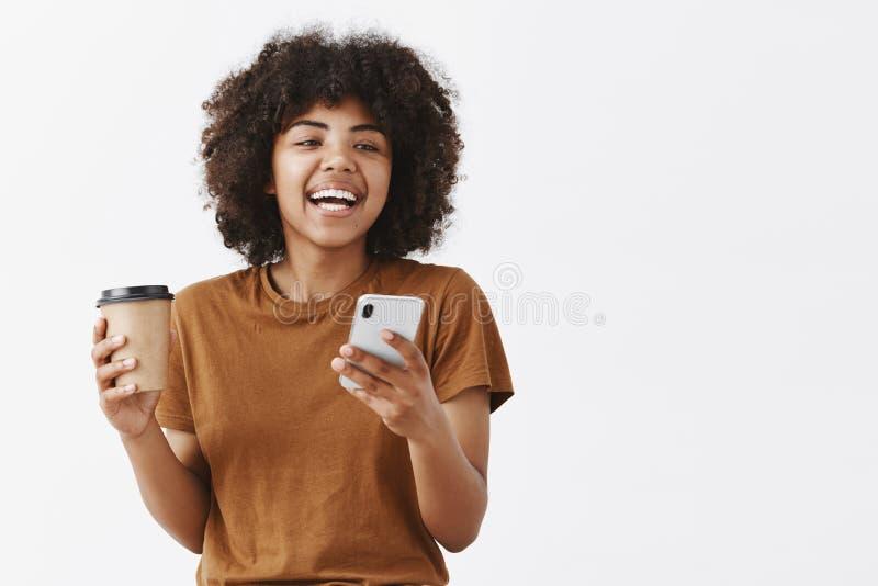A cintura-acima disparou da menina afro-americano despreocupada na moda com cabelo encaracolado no t-shirt marrom que ri ao falar imagens de stock royalty free