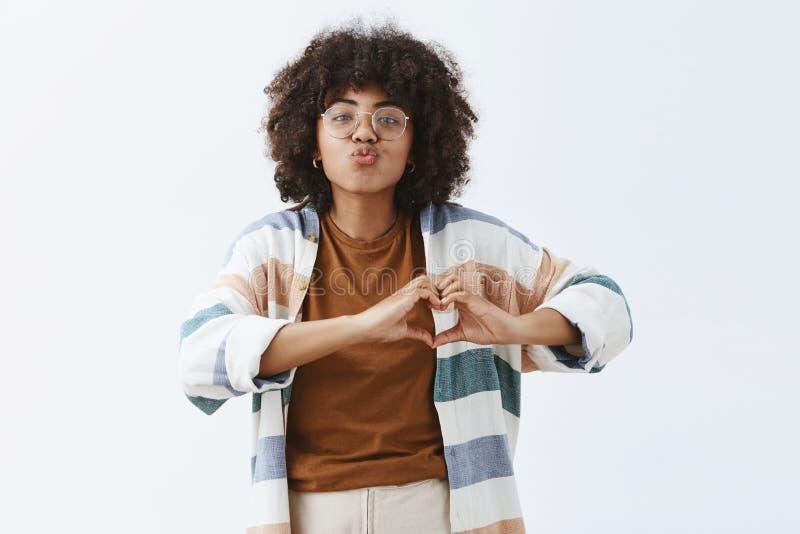 A cintura-acima disparou da mulher afro-americano sociável à moda e moderna nos vidros e na exibição listrada à moda do casaco de fotos de stock