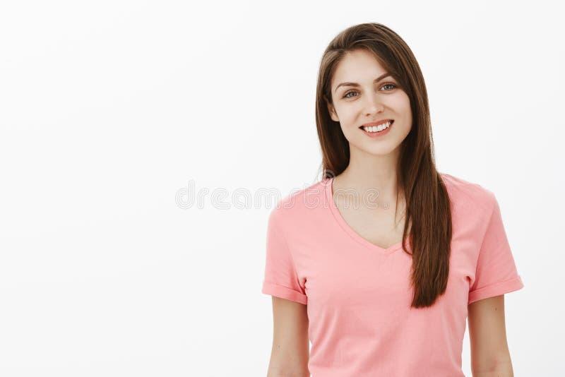 A cintura-acima disparou da mulher caucasiano bonita despreocupada feliz no t-shirt cor-de-rosa, sorrindo amplamente e olhando na fotos de stock