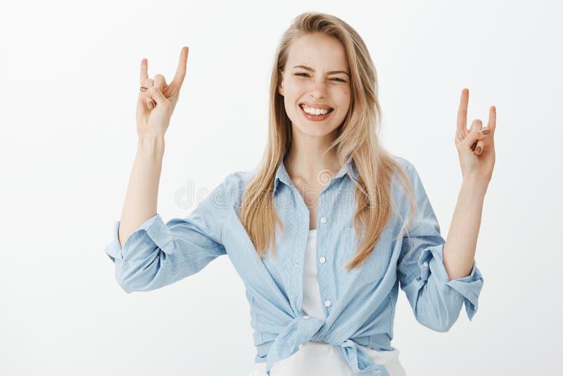 A cintura-acima disparou da mulher despreocupada feliz na camisa azul, levantando as mãos e mostrando gestos da rocha ao sorrir a foto de stock royalty free