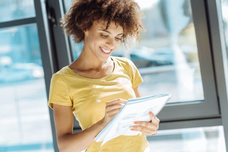 Cintura acima do estudante afro-americano fêmea alegre que planeia seu dia fotos de stock royalty free