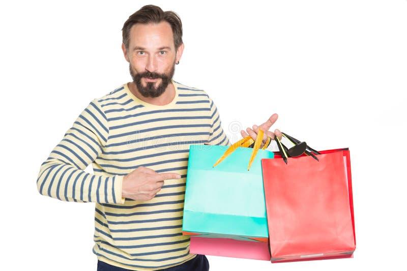 Cintura acima do homem shopaholic satisfeito que aponta em suas compras imagem de stock