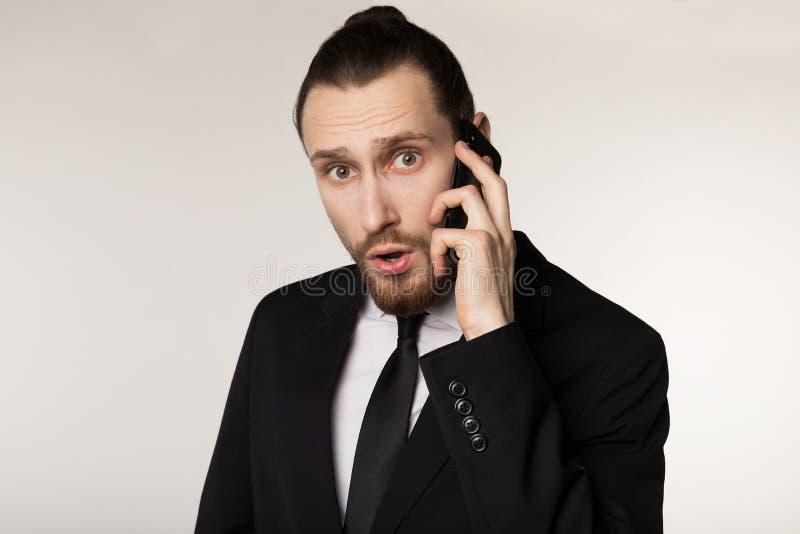 Cintura acima do retrato do homem de negócios novo farpado no terno preto surpreendido pela notícia ouvida de um sócio comercial imagens de stock