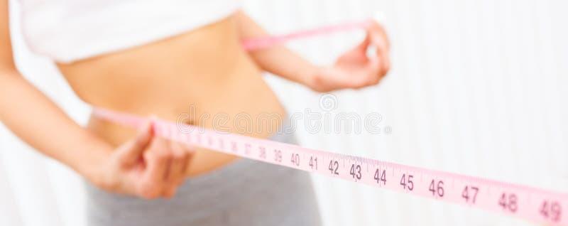 Cintura de medição da menina fêmea da mulher com fita métrica do panorama imagens de stock