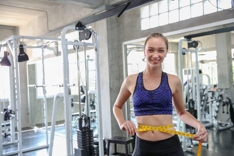 Cintura de medição da mulher no gym Mulher magro que mede seu wais fino imagem de stock royalty free