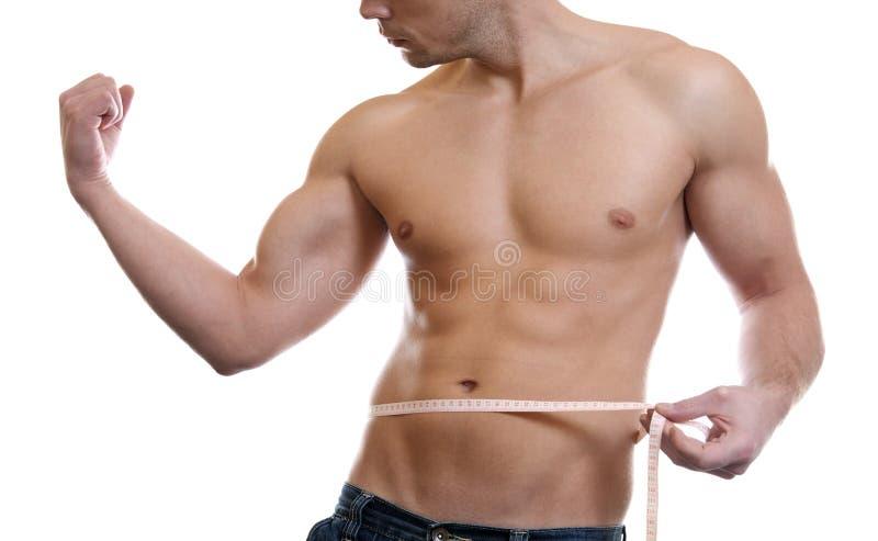 Cintura de medição do homem muscular fotos de stock