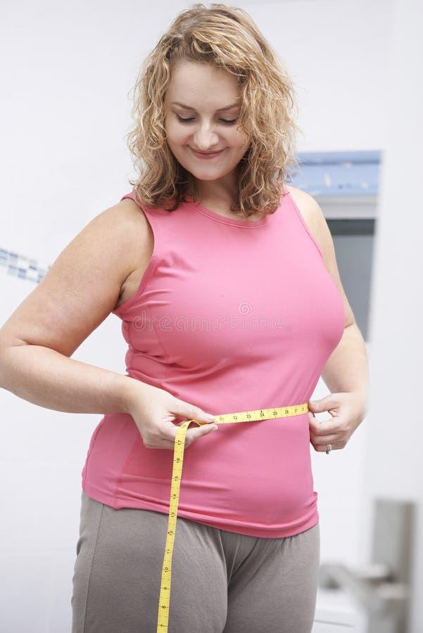 Cintura de medición de la mujer feliz del tamaño extra grande en cuarto de baño imagen de archivo libre de regalías