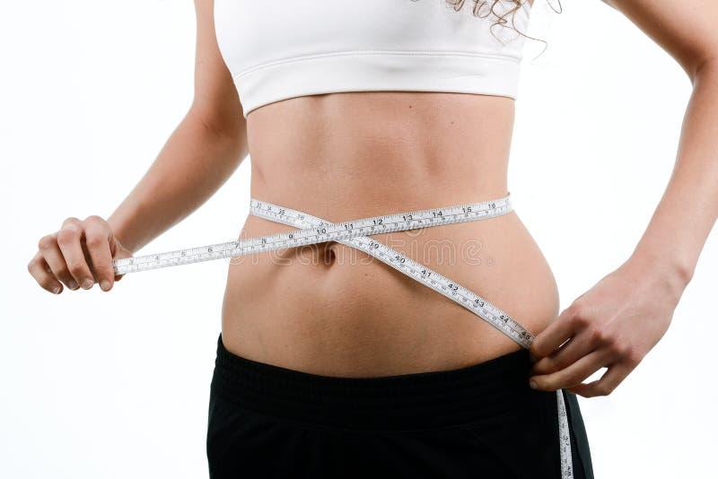 Cintura de medición de la mujer joven con la cinta en el fondo blanco imagenes de archivo