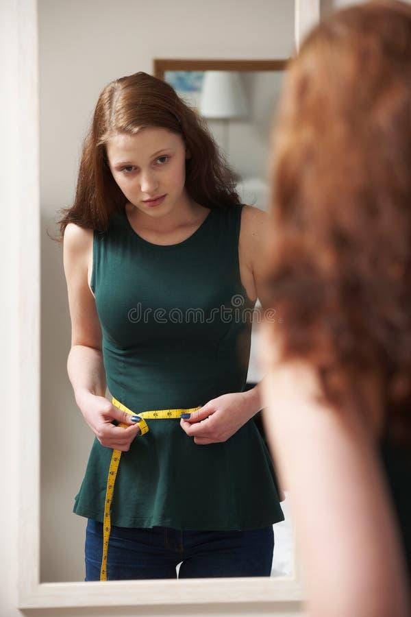 Cintura de medición del adolescente infeliz en espejo fotografía de archivo