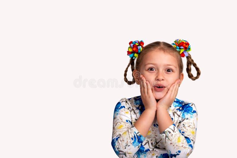 Cintura del estudio encima del retrato de una camisa que lleva de la niña con una impresión y con dos coletas y arcos del color e imagen de archivo