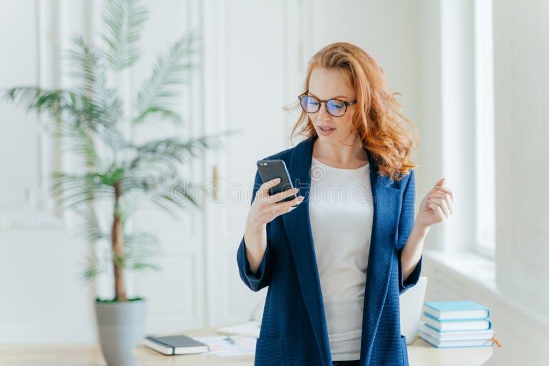 A cintura disparou acima da mulher de negócios bem sucedida usa a aplicação no telefone celular, lê o e-mail recebido do chefe ou imagens de stock royalty free