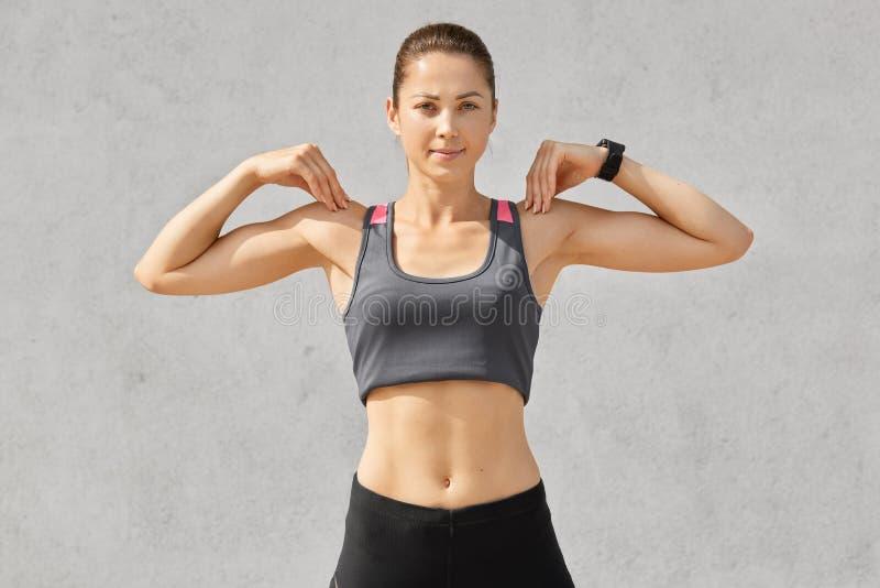 A cintura disparou acima da mulher desportiva mantém ambas as mãos em ombros, faz exercícios durante o exercício da manhã, veste  imagem de stock royalty free