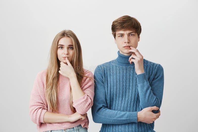 Cintura encima del retrato de los pares caucásicos jovenes que llevan los suéteres hechos punto que tienen expresiones pensativas imagen de archivo libre de regalías