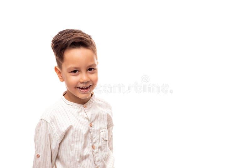 Cintura encima del retrato de un pequeño muchacho sonriente, aislado imagen de archivo