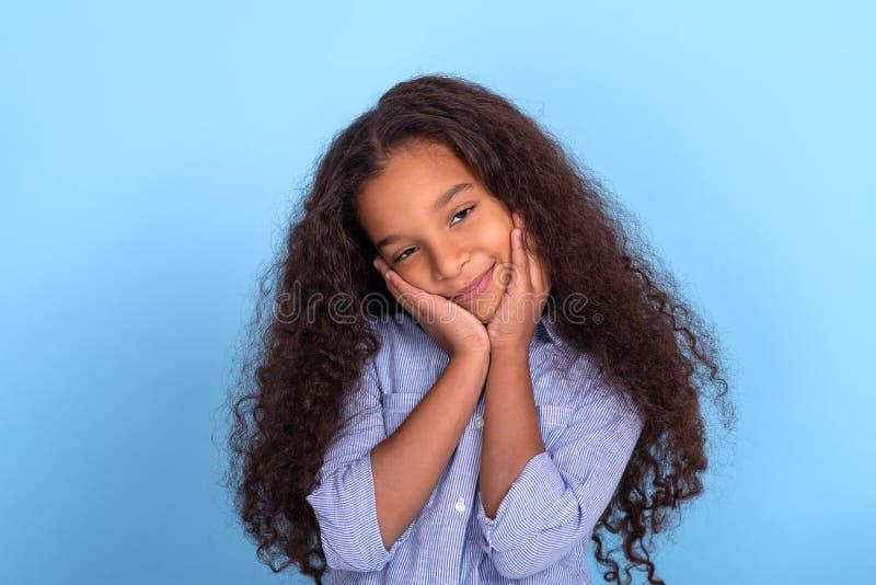 Cintura encima del retrato emocional de la muchacha muy rizada del mulatta que lleva la camisa azul en un fondo azul con el espac fotografía de archivo