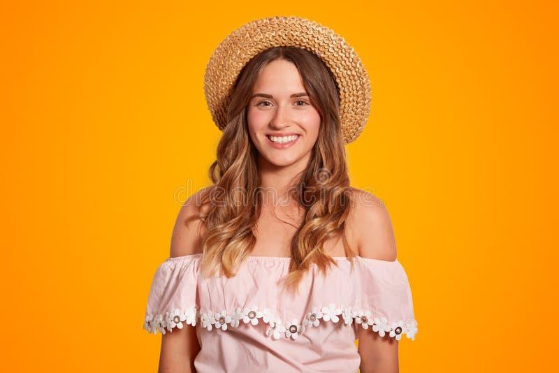 Cintura encima del retrato del viajero femenino joven hermoso encantado con sonrisa amplia, piel pura sana, vestida en sombrero d fotos de archivo