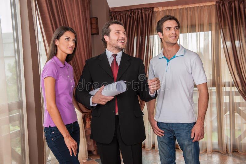 Cintura para arriba del agente inmobiliario de sexo masculino que sonríe con dos clientes fotos de archivo