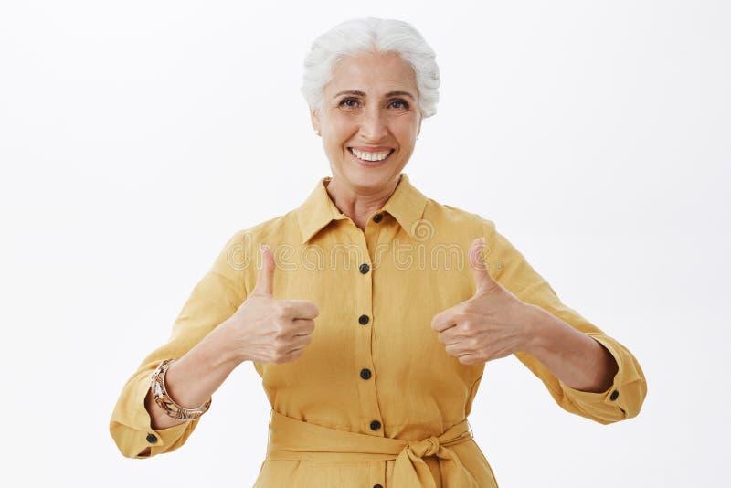 Cintura-para arriba tirada de clase pelased y de señora mayor elegante agradable en la capa amarilla de moda que muestra los pulg fotos de archivo libres de regalías