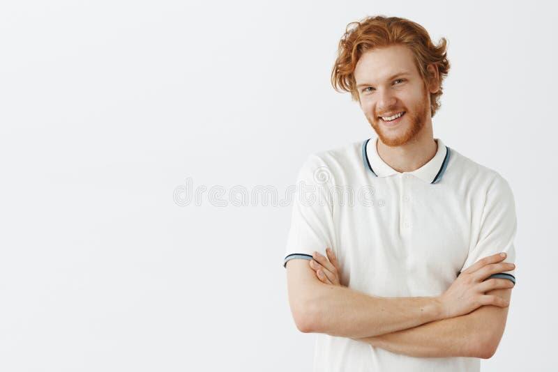 Cintura-para arriba tirada de individuo europeo lindo del pelirrojo con el pelo ondulado y de la barba que inclina el joyfull pri foto de archivo