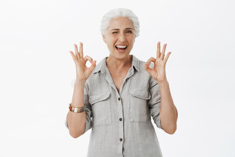 Cintura-para arriba tirada de la abuelita impresionante feliz y linda carismática que guiña alegre la sonrisa y mostrar los gesto fotografía de archivo