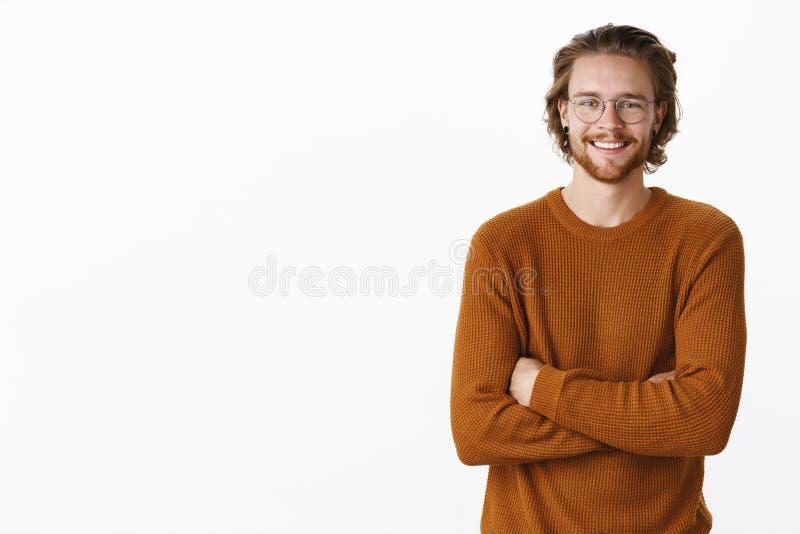 Cintura-para arriba tirada de varón europeo encantado de amistoso-mirada con el pelo largo y de barba en vidrios y suéter, llevan imagenes de archivo
