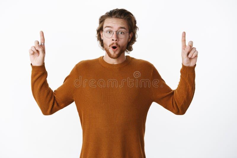 Cintura-para arriba tirada de varón joven hermoso emocionado e impresionado en el suéter y los vidrios que doblan los labios en g fotos de archivo