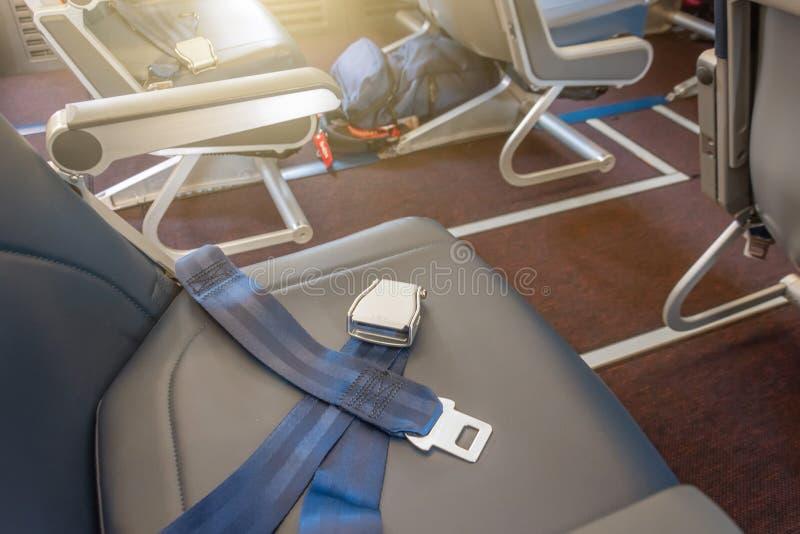 Cinture di sicurezza sul sedile del passeggero degli aerei Zaino del bagaglio a mano nell'ambito del sedile dell'aeroplano immagini stock libere da diritti