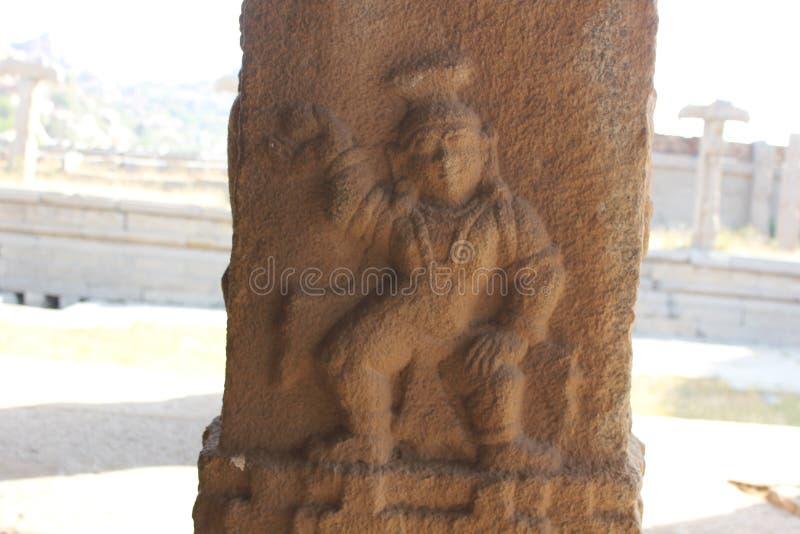 Cinzeladura da coluna da pedra do templo de Hampi Vittala de Krishna que guarda uma bola da manteiga foto de stock royalty free