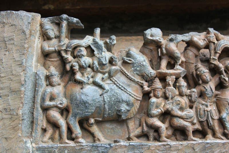 Cinzeladura da parede do templo de Hoysaleshwara do deus de Ishana do elemento do nordeste do sentido e da água que marcha em seu imagem de stock royalty free