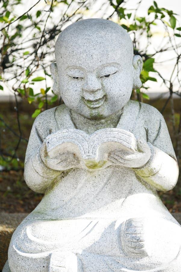Cinzeladura de pedra de uma meditação pequena de Buddha foto de stock