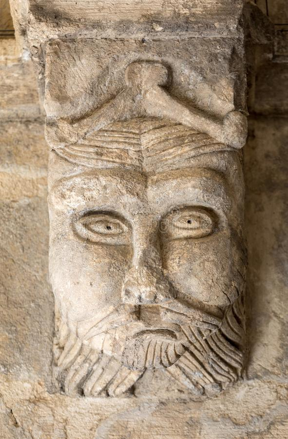 Cinzeladura românico de um capital estranho da cabeça ou da cara c12th nos claustros da abadia de Montmajour perto de Arles fotos de stock