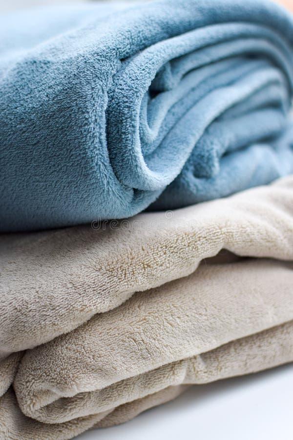 A cinzento-turquesa morna e o bege das mantas são dobrados sobre se fotos de stock