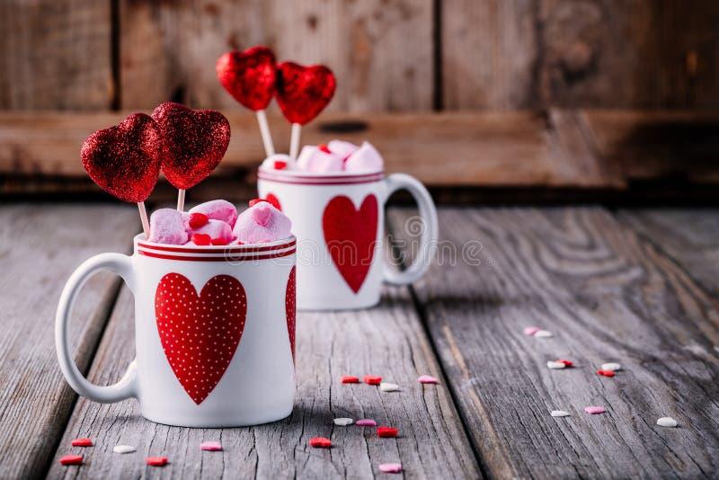 Cioccolata calda con la caramella gommosa e molle rosa in tazze con i cuori per il giorno di S. Valentino fotografia stock