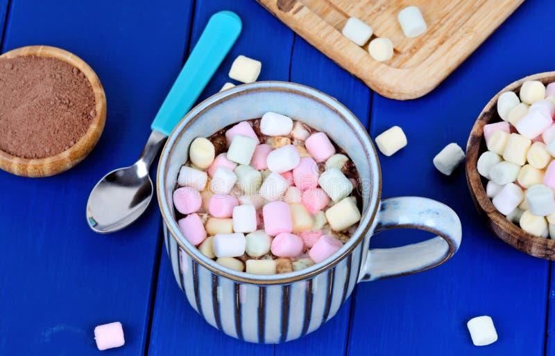 Cioccolata calda con la mini bevanda variopinta di inverno delle caramelle gommosa e molle sulla tavola fotografie stock libere da diritti