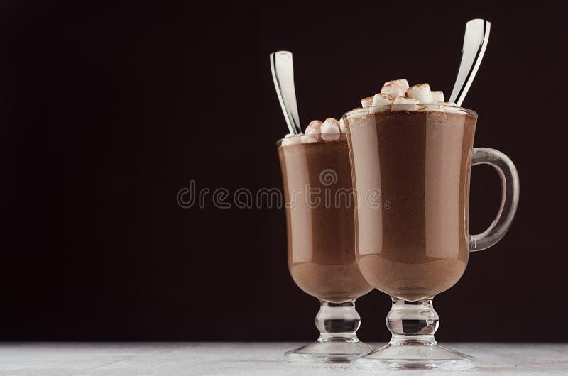 Cioccolata calda di eleganza in due vetri classici dell'irish coffee con le caramelle gommosa e molle ed i cucchiai d'argento sul immagini stock libere da diritti