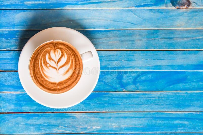 Cioccolata calda di vista superiore in tazza sulla tavola di legno blu fotografia stock