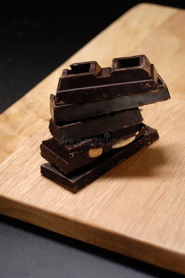 Cioccolato accatastato su un bordo di legno fotografie stock libere da diritti