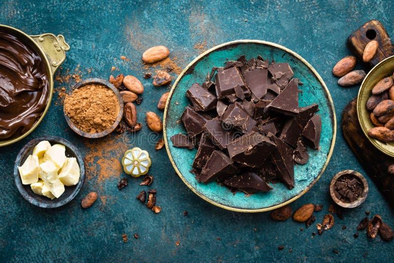 Cioccolato Bei pezzi del cioccolato amaro, burro del cacao, cacao in polvere e fave di cacao scuri Priorità bassa del cioccolato fotografia stock libera da diritti