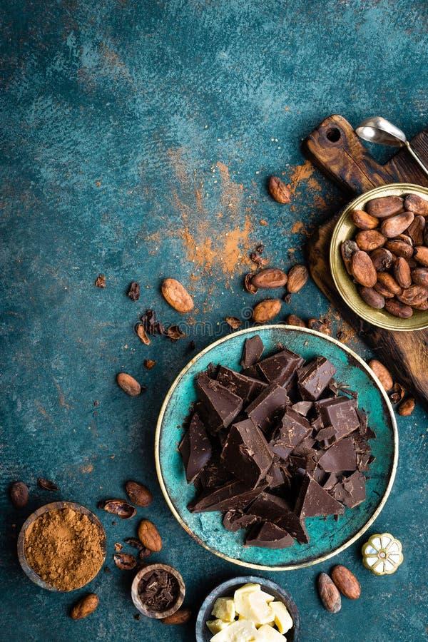 Cioccolato Bei pezzi del cioccolato amaro, burro del cacao, cacao in polvere e fave di cacao scuri Priorità bassa del cioccolato fotografie stock libere da diritti