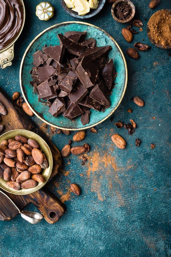 Cioccolato Bei pezzi del cioccolato amaro, burro del cacao, cacao in polvere e fave di cacao scuri Priorità bassa del cioccolato fotografia stock