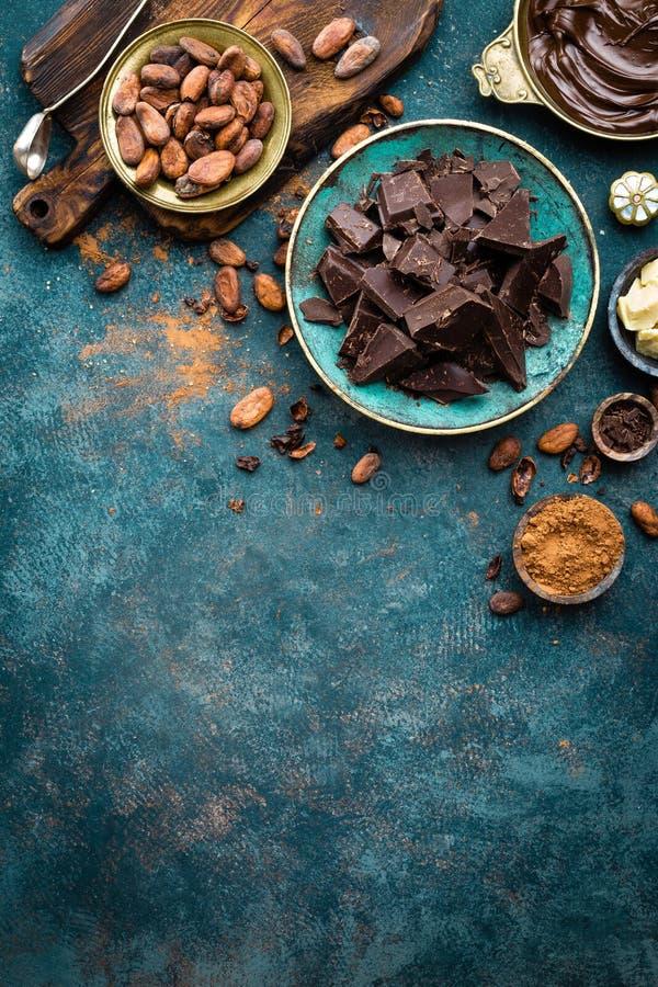Cioccolato Bei pezzi del cioccolato amaro, burro del cacao, cacao in polvere e fave di cacao scuri Priorità bassa del cioccolato immagini stock