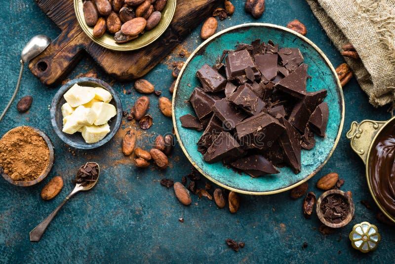 Cioccolato Bei pezzi del cioccolato amaro, burro del cacao, cacao in polvere e fave di cacao scuri Priorità bassa del cioccolato immagine stock
