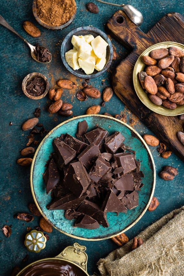 Cioccolato Bei pezzi del cioccolato amaro, burro del cacao, cacao in polvere e fave di cacao scuri Priorità bassa del cioccolato fotografie stock