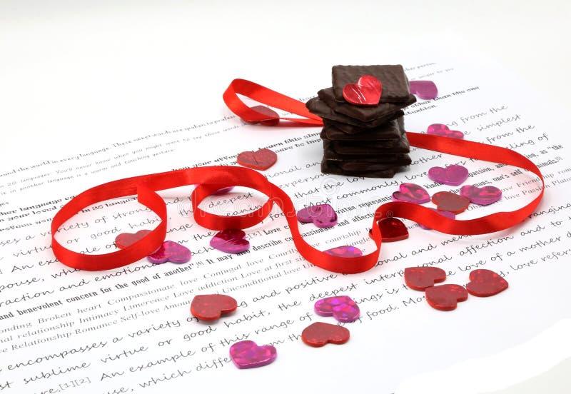 Cioccolato fondente impilato, cuori rosa di scintillio, nastro rosso sopra Libro Bianco con le parole scritte fotografia stock libera da diritti