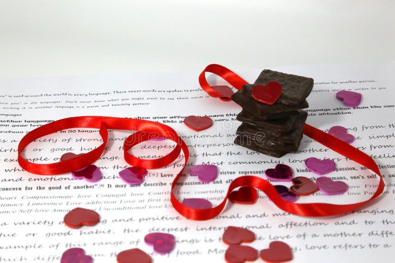 Cioccolato fondente impilato, cuori rosa di scintillio, nastro rosso sopra Libro Bianco con le parole scritte fotografia stock