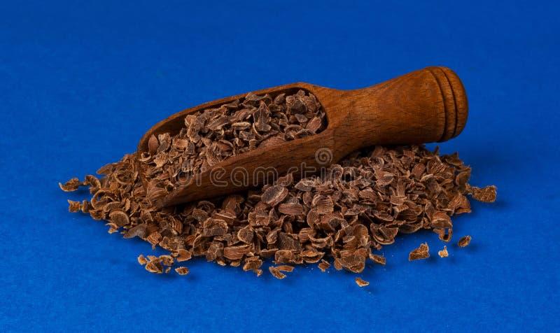Cioccolato grattato in mestolo di legno isolato sul fondo blu di colore, primo piano immagini stock